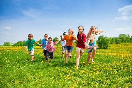 Photo for Large group of kids running in the dandelion spring field - Royalty Free Image
