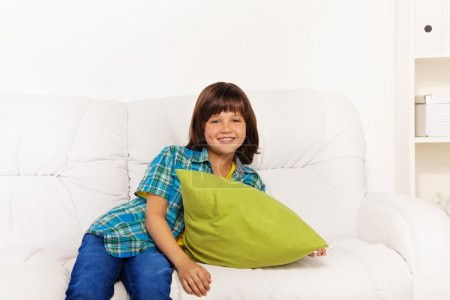 Photo for One happy calm and relaxed little boy 6 years old sitting with green pillow on the white leather coach in living room at home - Royalty Free Image
