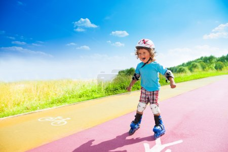 Happy boy rushing downhill on rollerblades