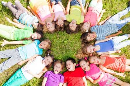 Photo for 14 kids laying in a circle in the grass with happy faces shoot from above - Royalty Free Image
