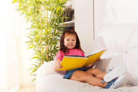 Foto de Chica poco inteligente 5 años tirado en el sofá y lectura - Imagen libre de derechos