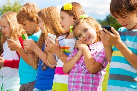 Photo pour Beau groupe de nombreux enfants debout avec les téléphones cellulaires parler d'envoyer des SMS et en jouant, tout à l'extérieur du - image libre de droit