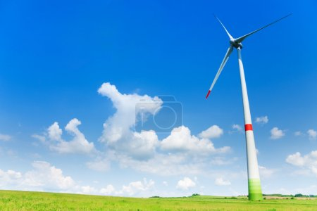 Foto de Turbina eólica en el campo con nubes en el cielo en un día soleado brillante - Imagen libre de derechos