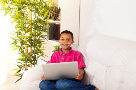 Foto de Chico lindo 8 años sentado en el sofá en casa con ordenador portátil sonriendo. - Imagen libre de derechos