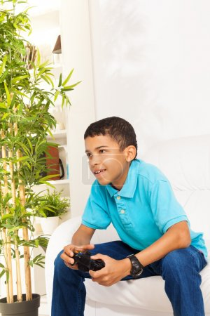 Photo for Happy black 10 years old boy playing video games holding game controller sitting on the white coach at home - Royalty Free Image