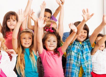 Foto de Closeup grupo retrato de siete feliz poco 5-6 años niños, niños y niñas, negras, asiáticos y caucásicos sentado en el sofá con las manos levantadas y caras felices - Imagen libre de derechos