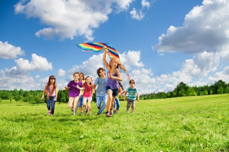 Photo for Cute happy active kids boys and girls run with kite in the park and having fun - Royalty Free Image