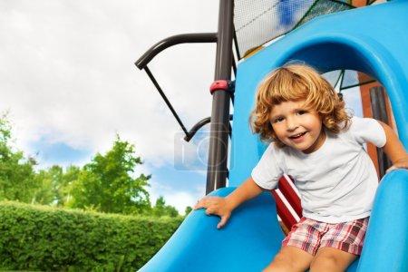 Foto de Retrato de niño de tres años de edad poco sonriente feliz a deslizar en patio azul de cierre - Imagen libre de derechos