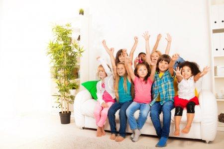 Foto de Grupo de los ocho feliz poco 5-6 años niños, niños y niñas, negras, asiáticos y caucásicos sentado en el sofá con las manos levantadas y caras felices - Imagen libre de derechos
