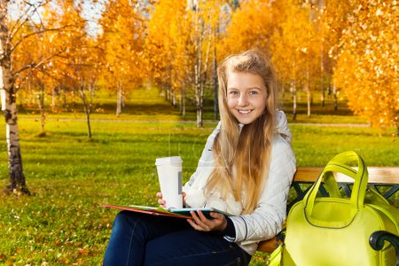 Photo pour Portrait rapproché d'une adolescente blonde souriante heureuse aux cheveux longs tenant du café et des livres et papiers avec sac posé sur le banc, dans un parc d'automne - image libre de droit