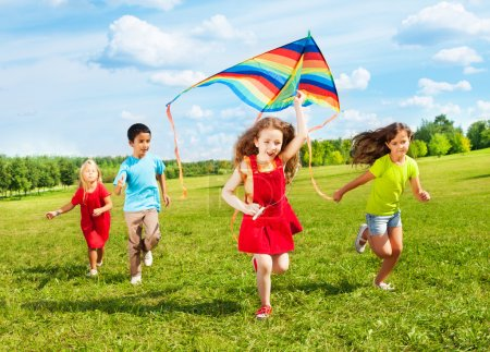Photo for Group of four kids run with kite in the park happy and smiling on summer sunny day - Royalty Free Image