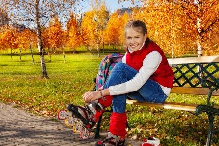 Photo pour Joyeux blond 11 ans fille avec un sourire incroyable mettre des patins à roulettes assis sur le banc dans le parc d'automne le jour ensoleillé - image libre de droit