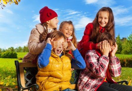 Photo pour Amis et surprise devinez qui action avec des filles, se cachant le visage garçons avec palmes en automne parc - image libre de droit
