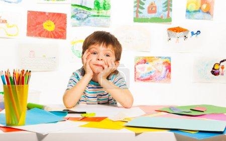 Foto de Nice three years old boy sitting in the class with pencils - Imagen libre de derechos