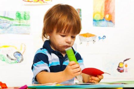 Foto de Lindas pequeña de 2 años chico en el arte de pegar hojas de cartulina de color - Imagen libre de derechos