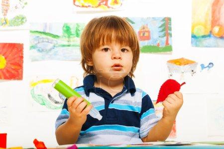 Foto de Lindas pequeña de 2 años chico en el arte de pegar hojas de papel de color - Imagen libre de derechos