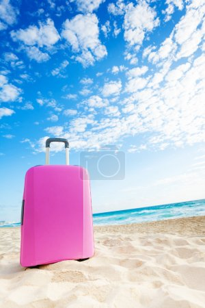 Pink suitcase bag on the beach