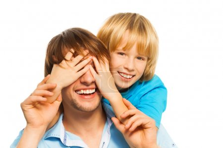 Foto de Joven feliz padre sonriente que adivina con la cara cubierta de hijo con las palmas - Imagen libre de derechos
