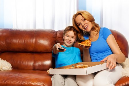 Boy and his mother eating pizza