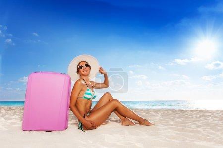 Photo pour Jeune femme séduisante assise sur la plage avec une jolie valise rose profitant du soleil portant un chapeau de paille et des nuances - image libre de droit