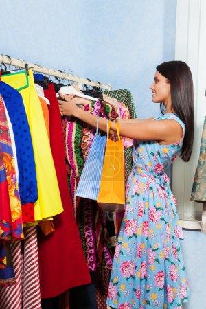Photo pour Belle jeune femme recherche des vêtements suspendus dans une rangée dans le centre commercial - image libre de droit