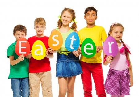 Photo pour Enfants tenant des cartes colorées en forme d'oeuf avec des lettres dans une rangée faisant mot Pâques ensemble - image libre de droit