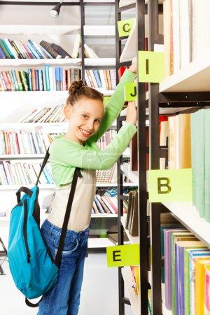 Photo pour Écolière avec sac bleu, la recherche de livres et la tenue des cahiers d'exercices sur l'étagère de la bibliothèque - image libre de droit