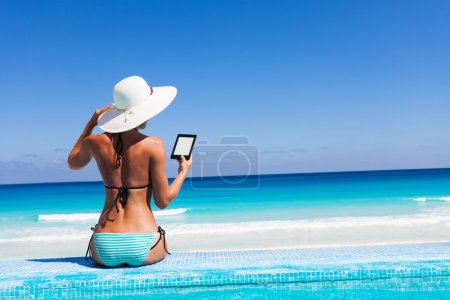 Girl with white hat reads kindle on beach