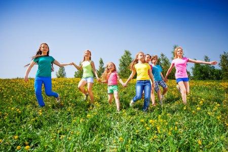 Photo pour Enfants heureux courir et se tenir la main dans la prairie verte pendant l'été - image libre de droit