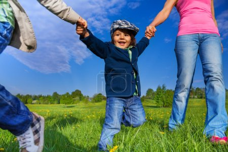 Happy kid holding parents hands in park