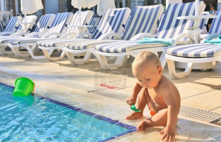 Kid playing in pool in hotel on background of of b...
