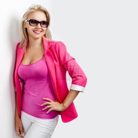 Photo pour Femme heureuse portant des lunettes de soleil et une veste rose - image libre de droit