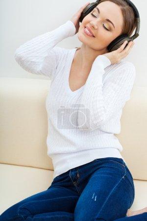 Photo pour Brunette femme sur le canapé écouter de la musique avec les yeux fermés - image libre de droit