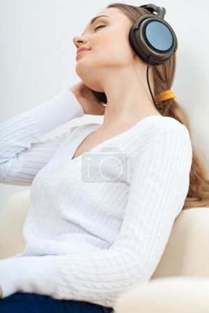 Photo for Brunette woman on the sofa listening to music with closed eyes - Royalty Free Image