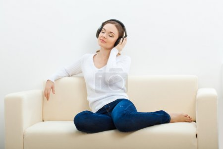 Woman on the sofa listening to music