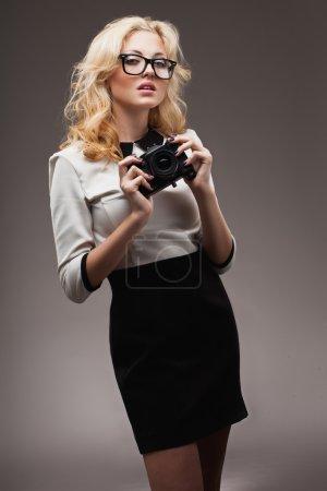 Blonde girl with camera wearing eyeglasses
