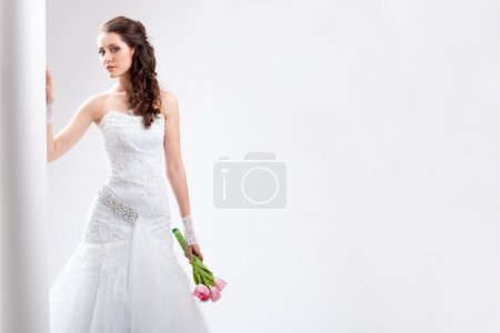 Beautiful bride standing near white column