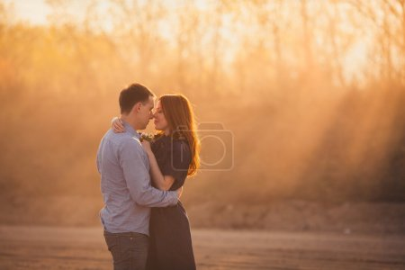 Couple embracing standing on the road in the dust