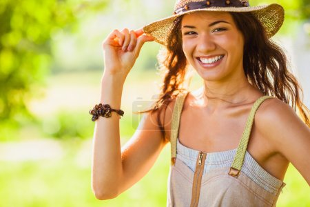 Photo for Happy girl wearing straw walking in the green summer park, closeup portrait - Royalty Free Image