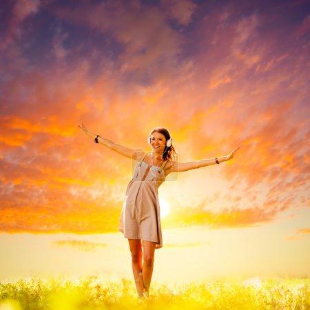 Photo pour Belle fille portant des écouteurs marchant sur le coucher du soleil - image libre de droit