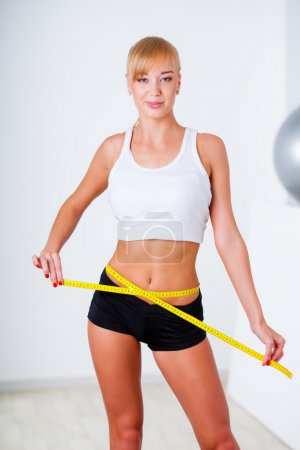 Blonde woman measuring her waistline