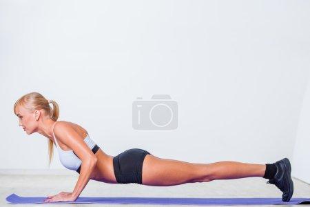 Blonde woman doing push-ups