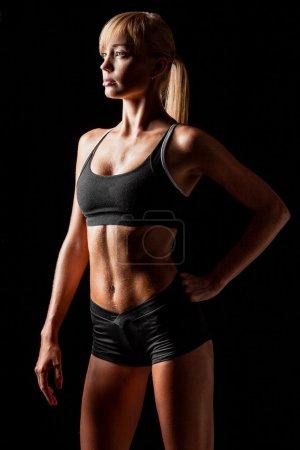 Photo for Sports woman portrait wearing black sportswear over dark - Royalty Free Image