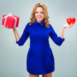 Happy blonde woman wearing blue dress holding red ...