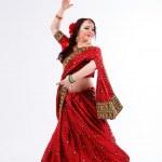 European brunette girl in red indian saree dancing...