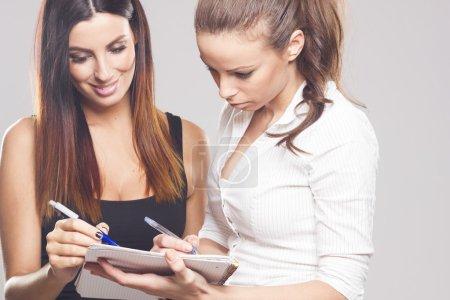 Two beautiful businesswomen in studio