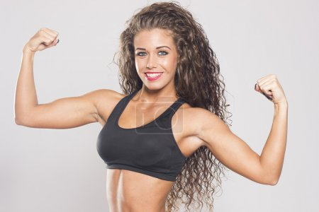 Sexy fitness woman flexing muscles