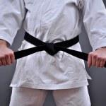 Man in martial arts uniform holding his black belt...