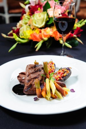 Juicy roe steak on a plate and glass of red wine