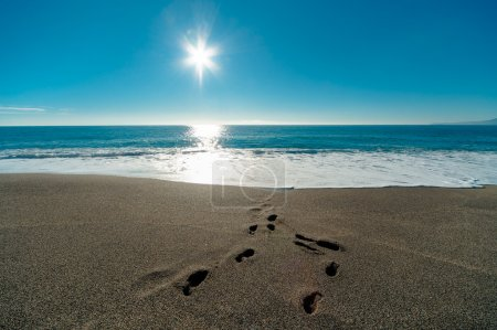 Sunny day, blue sea and footprints in the sand
